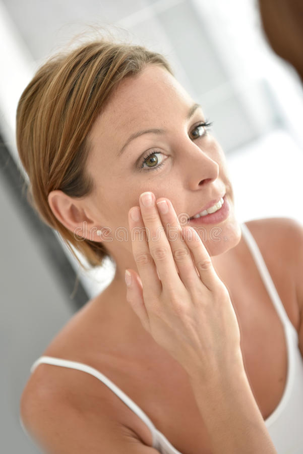 Young woman in front of mirror applying cream. Woman applying facial cream on her face stock photos