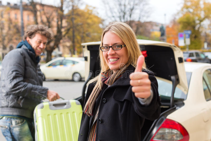 Young woman in front of taxi royalty free stock photo