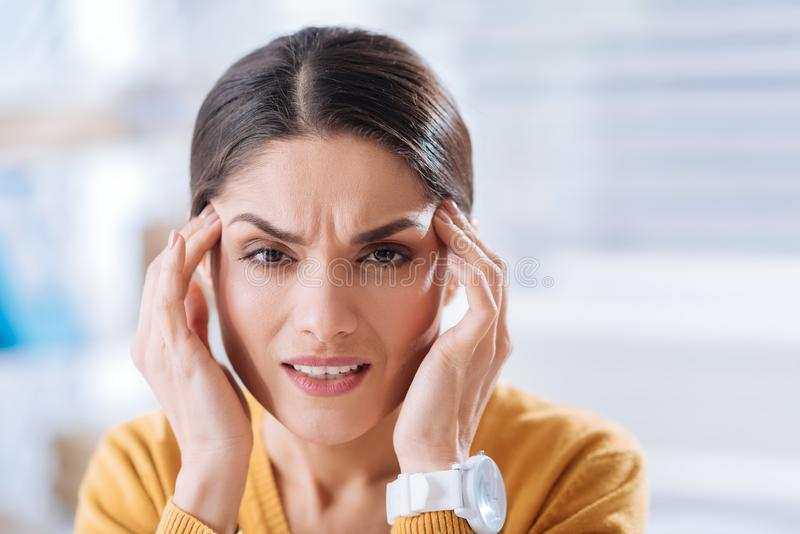 Young woman frowning while having a very painful migraine. Terrible migraine. Tired young frowning woman touching her forehead and feeling awful while having a royalty free stock photography