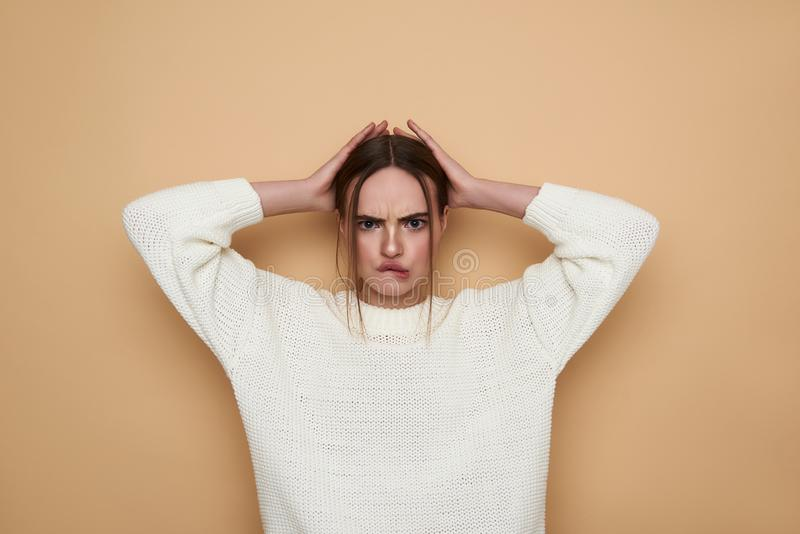 Young woman frowning and putting hands on her head royalty free stock images
