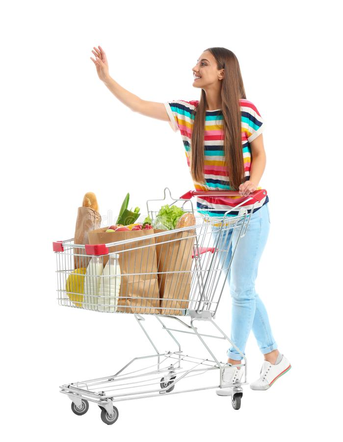 Young woman with full shopping cart on background. Young woman with full shopping cart on white background stock photos