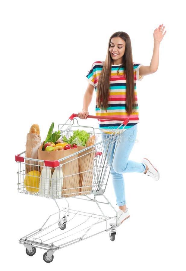 Young woman with full shopping cart on background. Young woman with full shopping cart on white background royalty free stock photography