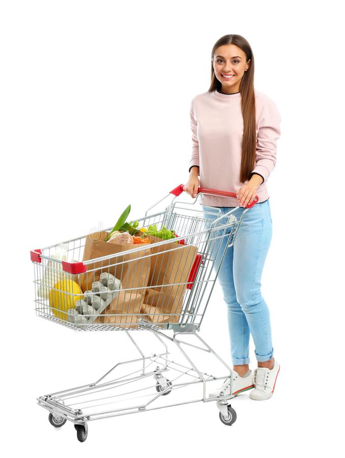 Young woman with full shopping cart on background. Young woman with full shopping cart on white background stock photography