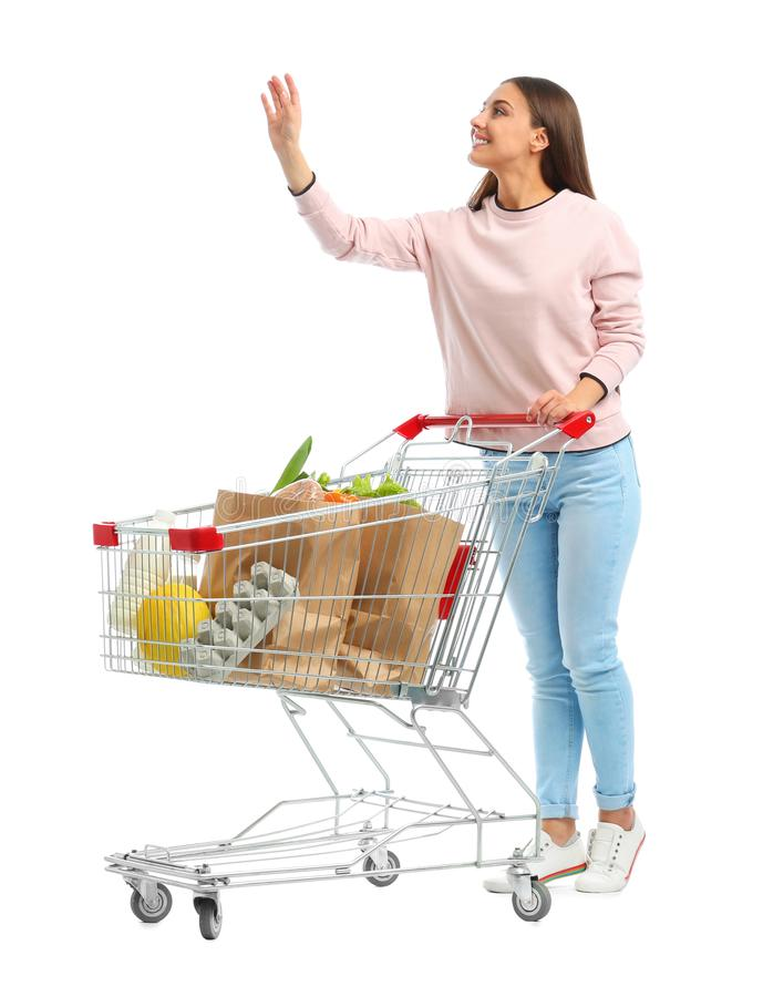 Young woman with full shopping cart on  background. Young woman with full shopping cart on white background stock images