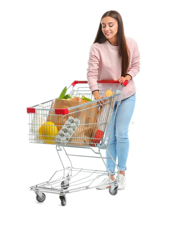 Young woman with full shopping cart on  background. Young woman with full shopping cart on white background royalty free stock photos