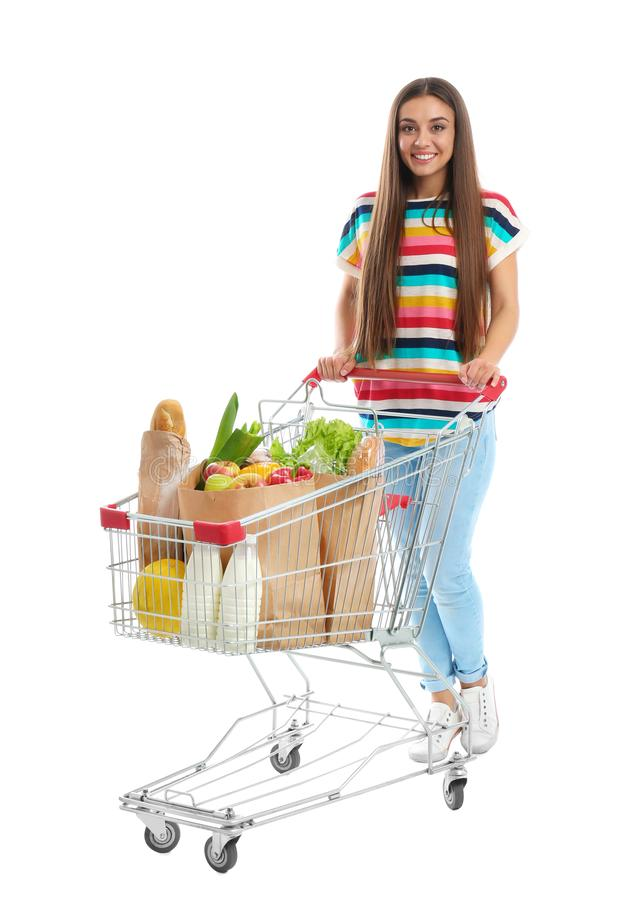 Young woman with full shopping cart on background. Young woman with full shopping cart on white background stock photo