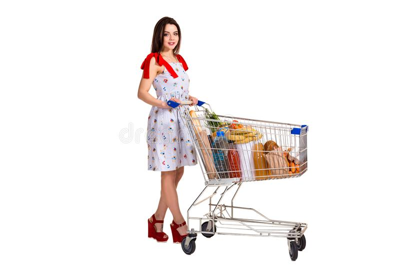 Young woman with full shopping cart on white background royalty free stock photos