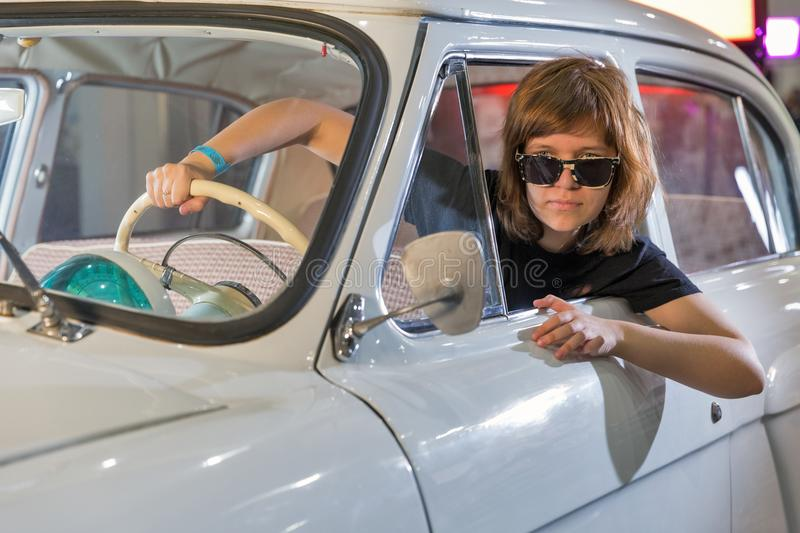 TV and Radio International Fair in Kiev, Ukraine. Young woman in GAZ-21 Volga vintage car on School of Authors Cinema and TV booth during TV and Radio stock photography
