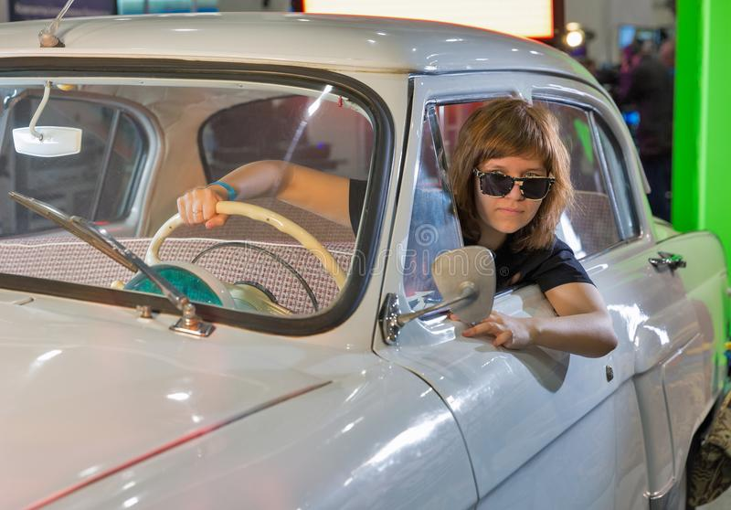 TV and Radio International Fair in Kiev, Ukraine. Young woman in GAZ-21 Volga vintage car on School of Authors Cinema and TV booth during TV and Radio royalty free stock images