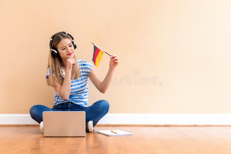 Young woman with Germany flag using a laptop computer royalty free stock images