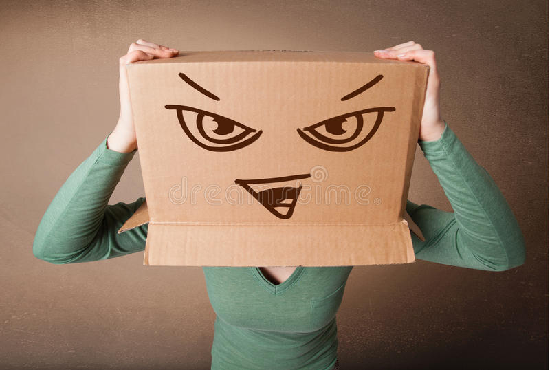 Young woman gesturing with a cardboard box on her head with evil. Young woman standing and gesturing with a cardboard box on her head with evil face royalty free stock photos