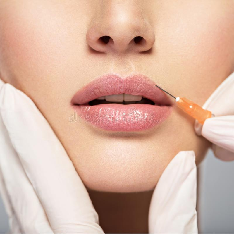 Young woman gets botox injection in her lips royalty free stock images