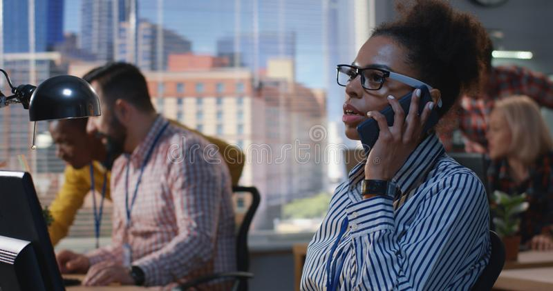 Young woman getting a call at an office royalty free stock photos