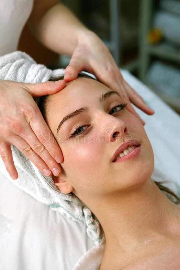 Young woman getting a face massage royalty free stock photography