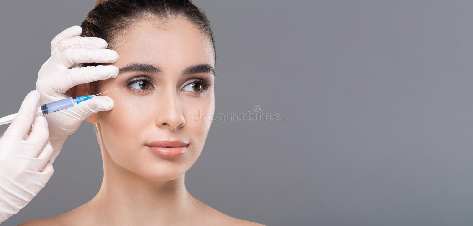 Young woman getting facial beauty injection, panorama. Cosmetology. Young woman getting facial beauty injection, panorama with empty space stock photos
