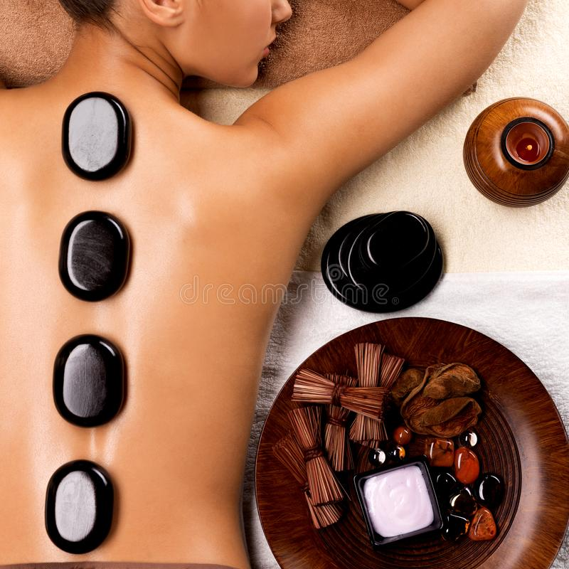 Young woman getting hot stone massage in spa salon. Portrait of young woman getting hot stone massage in spa salon. Beauty treatment concept royalty free stock photos