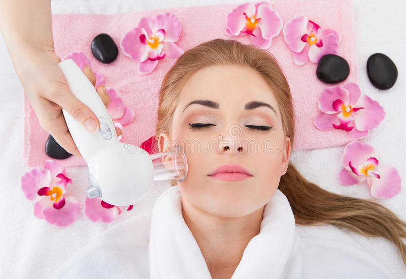 Young woman getting laser therapy. High Angle View Of Young Woman Getting Laser Therapy In Spa royalty free stock photos