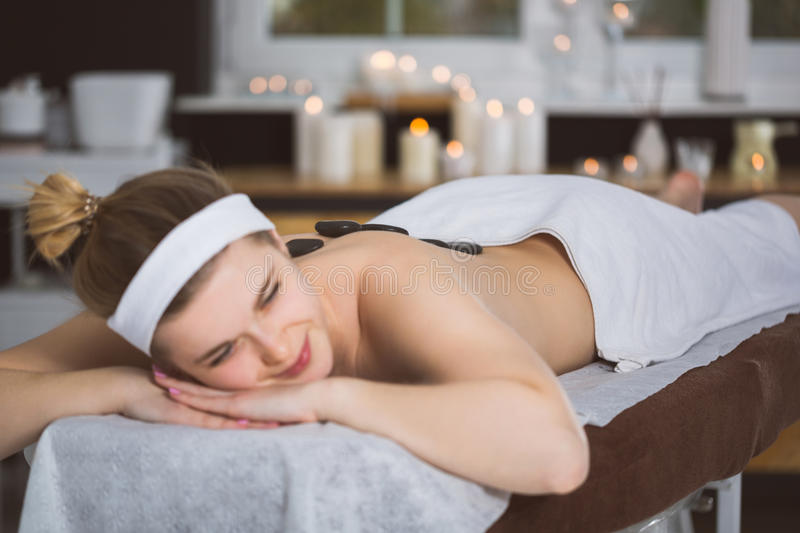 Young woman getting lastone therapy in spa. Blonde woman relaxing in spa with hot stones on her back royalty free stock photo