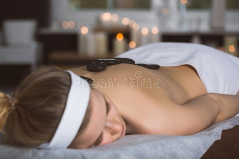 Young woman getting lastone therapy in spa. Blonde woman relaxing in spa with hot stones on her back stock image