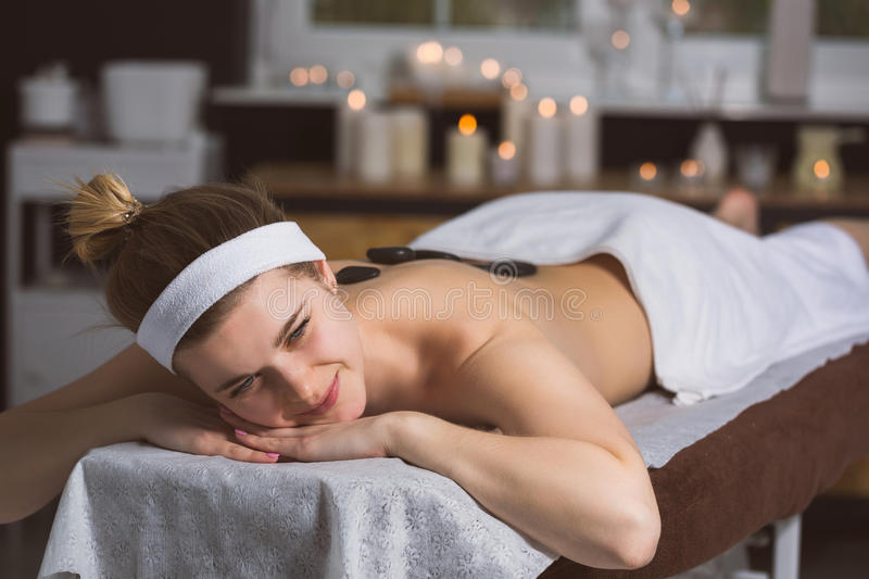 Young woman getting lastone therapy in spa. Blonde woman relaxing in spa with hot stones on her back stock images