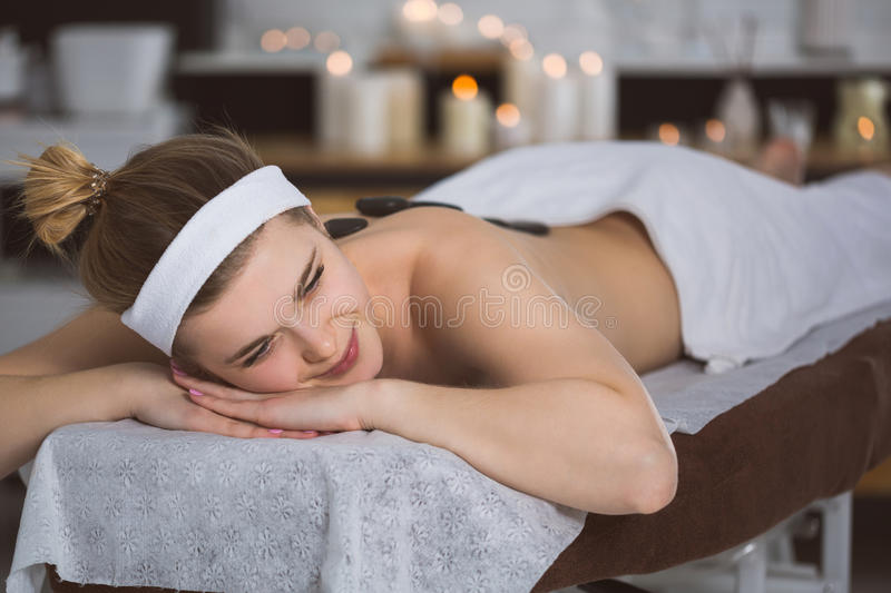 Young woman getting lastone therapy in spa. Blonde woman relaxing in spa with hot stones on her back royalty free stock image