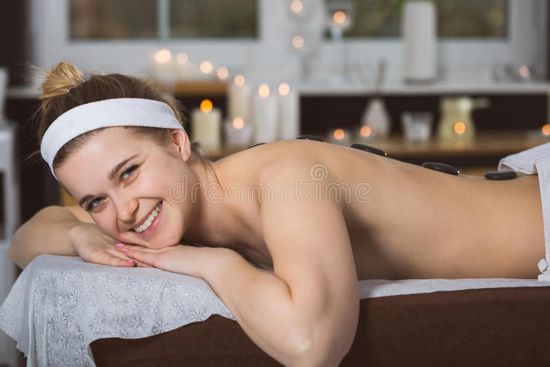 Young woman getting lastone therapy in spa. Blonde woman relaxing in spa with hot stones on her back stock photos