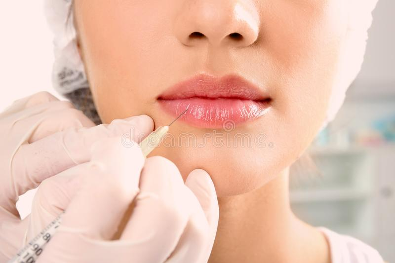 Young woman getting lip injection in beautician salon stock photo