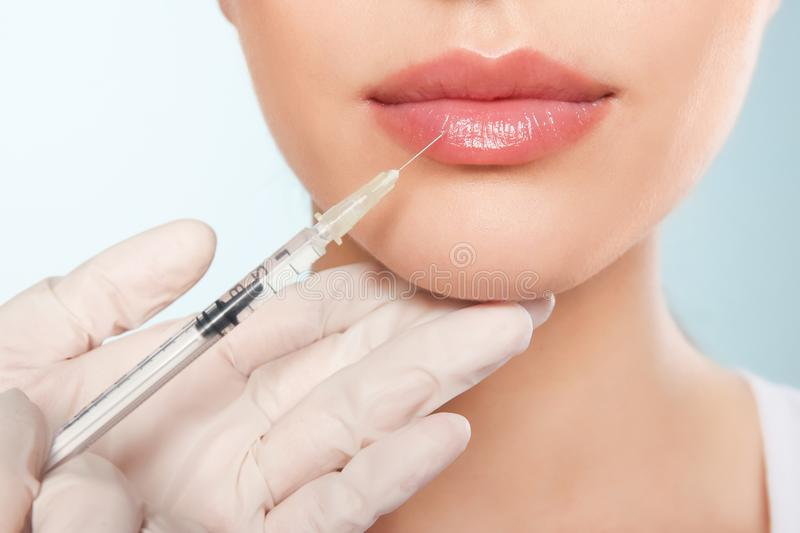 Young woman getting lip injection on color background royalty free stock image