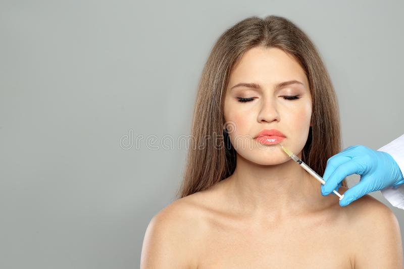 Young woman getting lips injection on grey background, space for text. royalty free stock photography