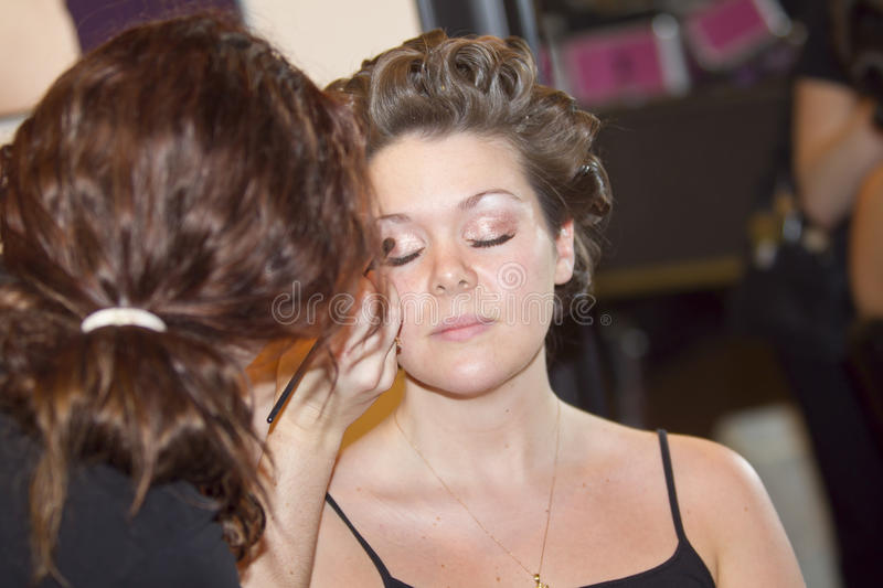Young woman getting makeup done