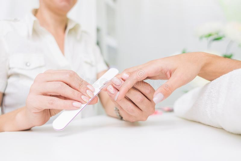 Young woman getting manicure in beauty salon. Close-up royalty free stock photos