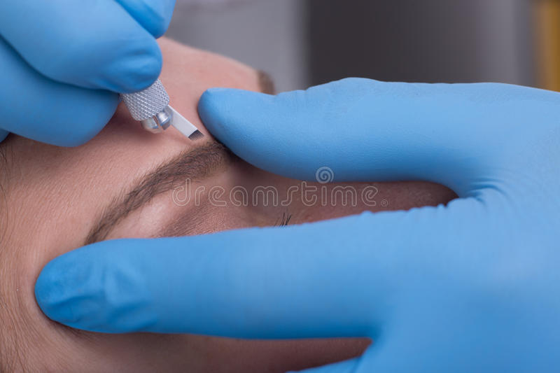 Young woman getting a permanent eyebrow make up treatment royalty free stock photos