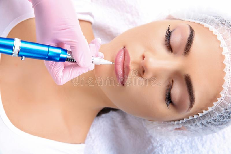 Young woman getting permanent makeup on lips royalty free stock photography