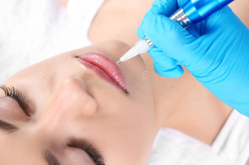 Young woman getting permanent makeup on lips royalty free stock photo