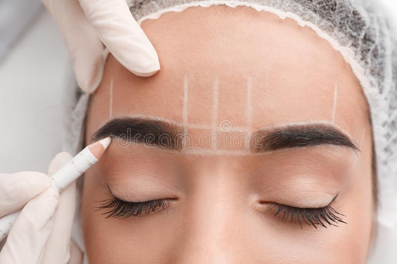 Young woman getting prepared for procedure of permanent eyebrow makeup in tattoo salon. Closeup stock image