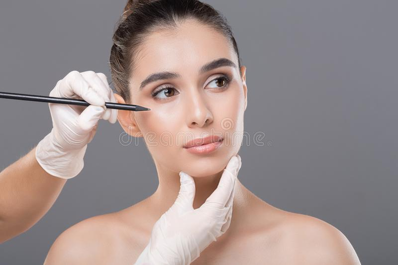 Young woman getting ready for face lifting. Aesthetic cosmetology. Young woman getting ready for face lifting, free space royalty free stock images