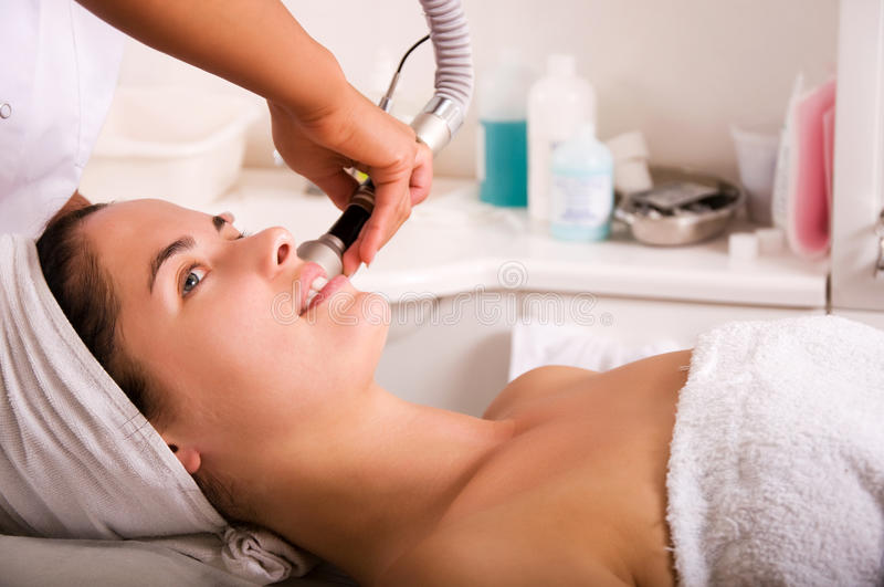 Young woman getting skin cleaning at beauty salon stock photography