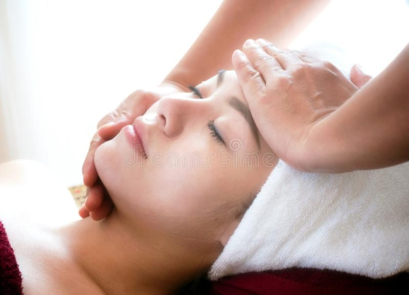 young woman getting spa face massage at beauty salon. stock photos