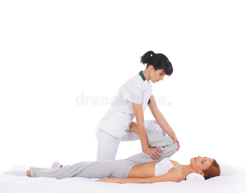 A young woman getting a traditional Thai massage. A young and attractive redhead women getting a traditional Thai massage from a female therapist. The image is royalty free stock photography