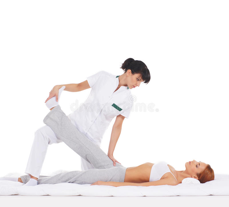 A young woman getting a traditional Thai massage. A young and attractive redhead women getting a traditional Thai massage from a female therapist. The image is stock image