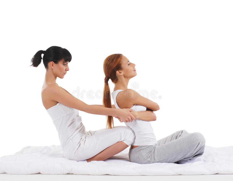 A young woman getting a traditional Thai massage. A young and attractive redhead women getting a traditional Thai massage from a female therapist. The image is royalty free stock images