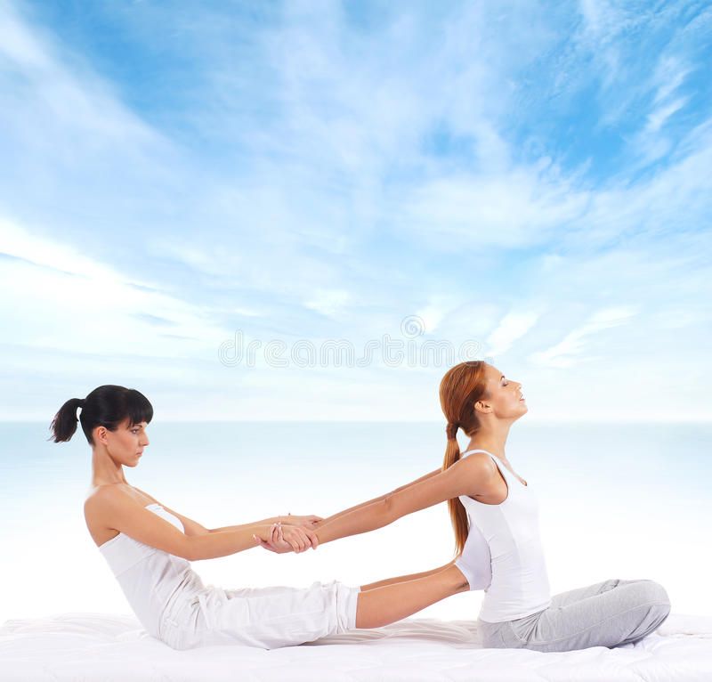 A young woman getting a traditional Thai massage. A young and attractive redhead women getting a traditional Thai massage from a female therapist. The image is royalty free stock photos