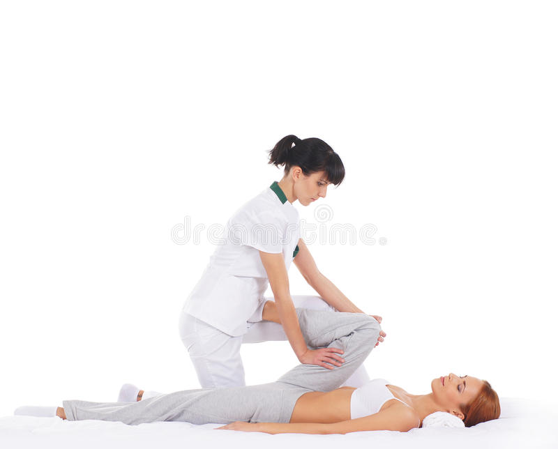 A young woman getting a traditional Thai massage. A young and attractive redhead women getting a traditional Thai massage from a female therapist. The image is stock photos