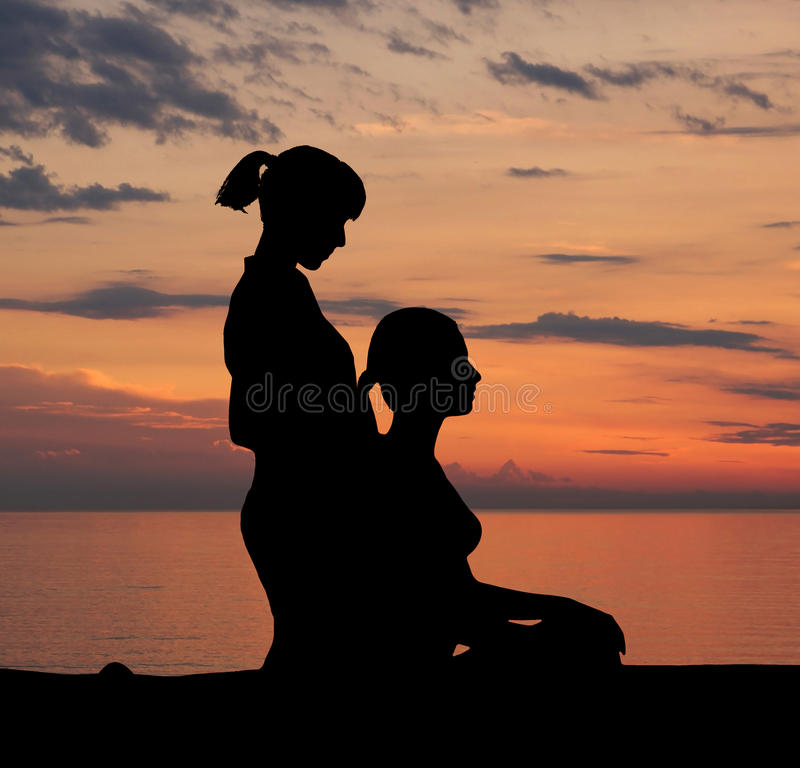 Trace of young woman getting traditional thai stretching massage by therapist isolated on the sunset background.  royalty free stock photography