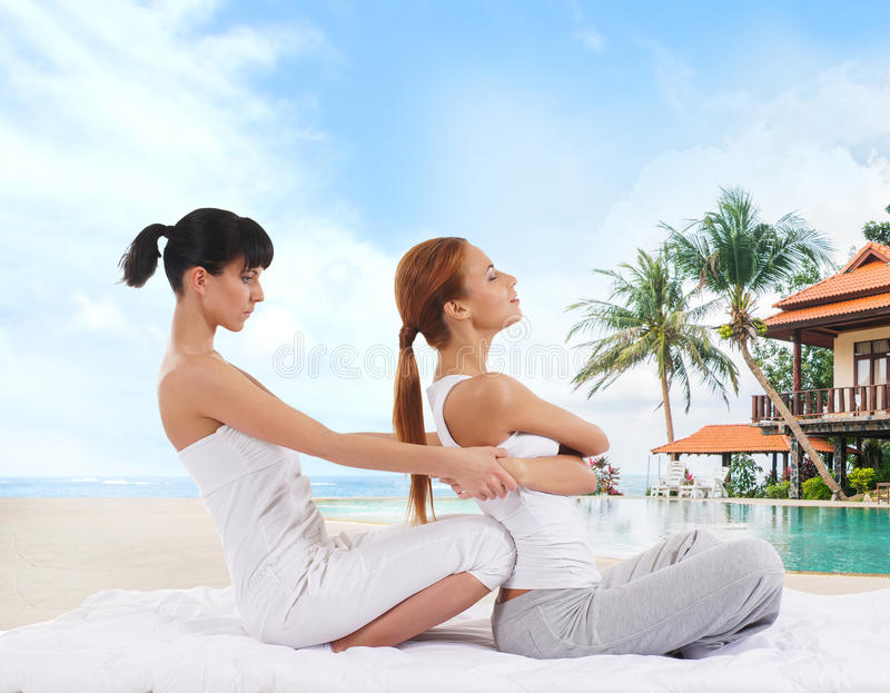 Young woman getting traditional Thai stretching massage by therapist over marine landscape. Young women getting traditional Thai stretching massage by therapist royalty free stock photo