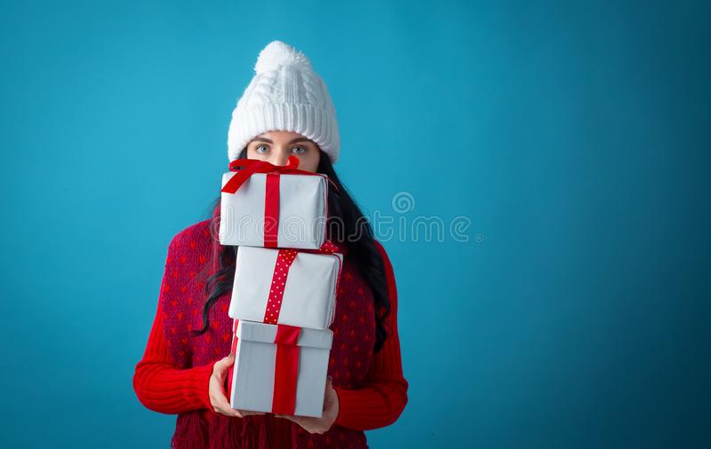 Young woman with gift boxes. On a dark blue background royalty free stock photos