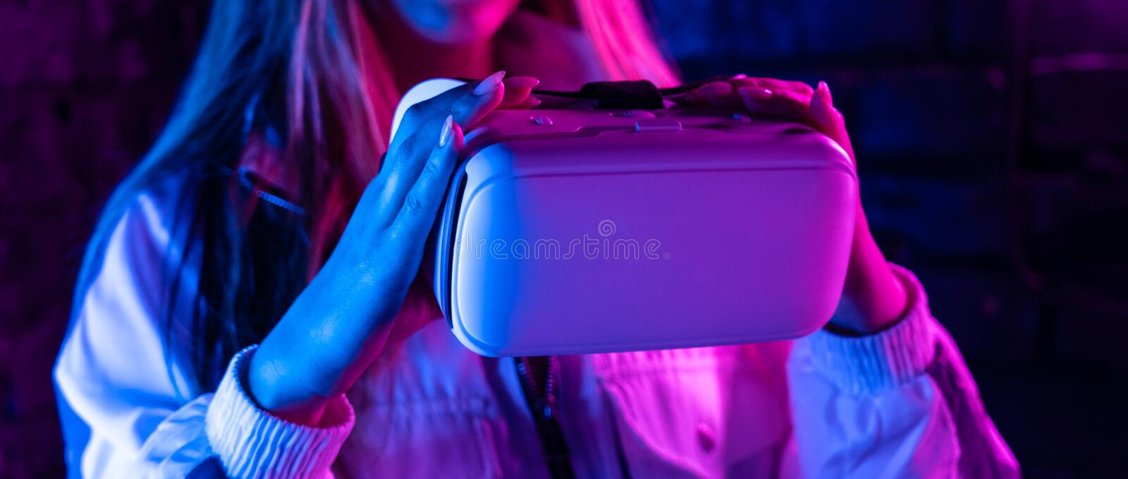 Girl gamer hold vr glasses goggles in futuristic purple neon light, banner royalty free stock photos