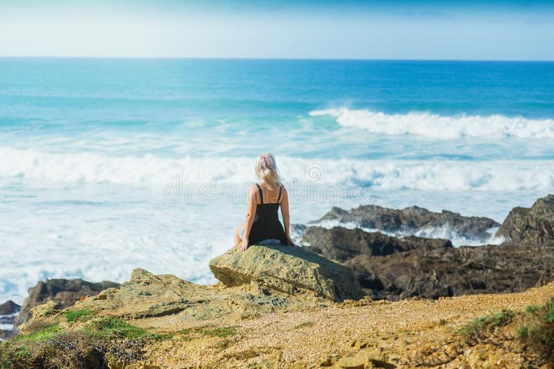 Young woman or girl looks at sea from rocks stock photo