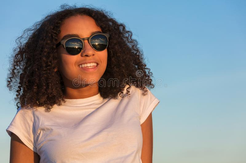 Young Woman Girl Teenager Wearing Sunglasses at Sunset. Mixed race biracial African American girl teenager female young woman with perfect teeth, sitting at stock photos