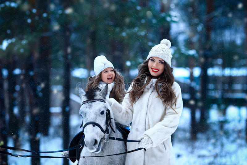 Young woman and girl walk with miniature horse in winter park. Young women and girl walk with miniature horse in winter park stock photo